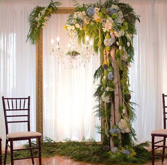 a vintage picture frame with a crystal chandelier, birch branches, pinecones, greenery and blooms for a woodland feel indoors