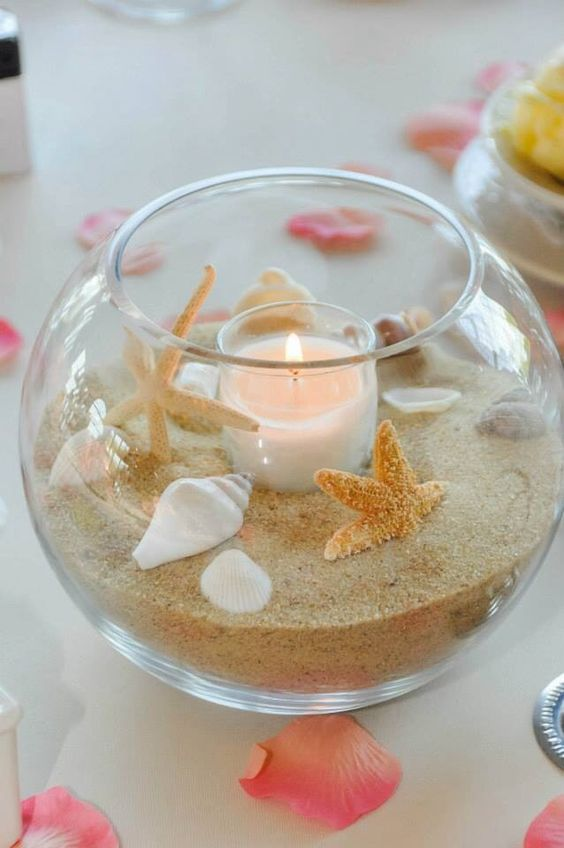 a glass bowl with beach sand, shells, starfish and a blush candle is a perfect fit for a beach wedding