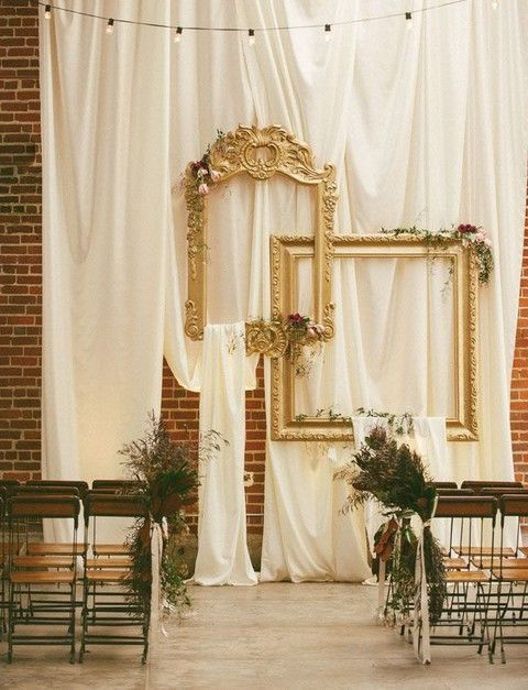 draped fabric and vintage refined picture frames for a vintage-inspired wedding