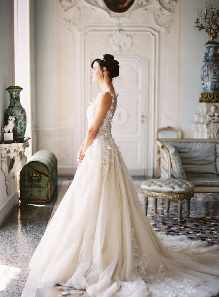 The bride was wearing a beautiful lace applique wedding dress with a train and an illusion neckline