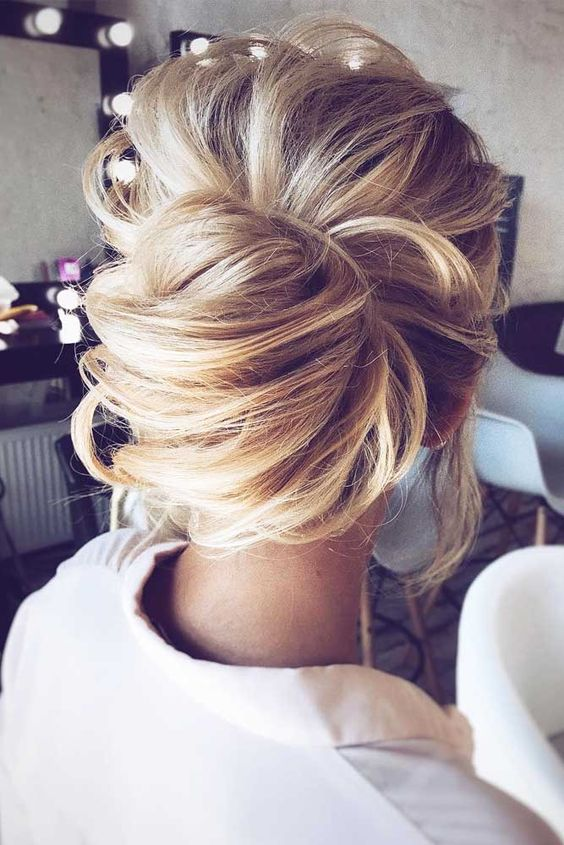 messy chignon hairstyle with a voluminous top and bangs for a modern wedding