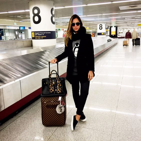 black jeans, black slip-ons, a grey sweatshirt with a penguin, a black scarf and coat
