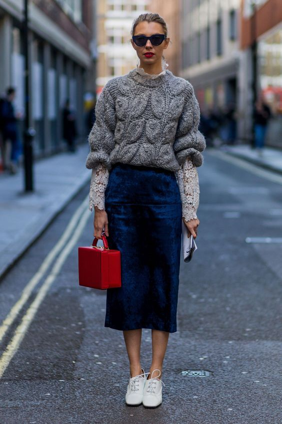 a navy velvet midi skirt, a grey sweater over a lace shirt, white sneakers and a red bag