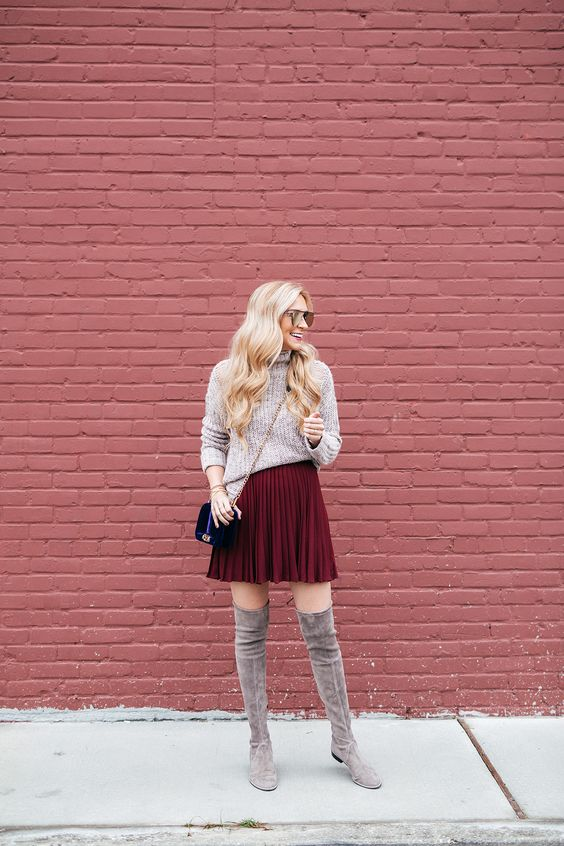 a neutral turtleneck sweater, a burgundy pleated mini skirt, grey flat suede tall boots