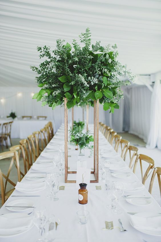 a lush greenery and foliage wedidng centerpiece on a tall metallic stand for a modern wedding