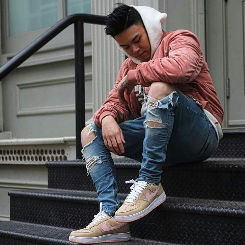 With white hoodie, distressed jeans and beige sneakers