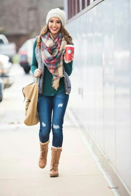 With green shirt, distressed jeans, mid calf boots, white beanie and gray puffer vest