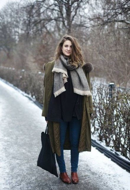 a layered look with a black sweater, a grey scarf, blue denim, an olive green coat and cognac chelsea boots