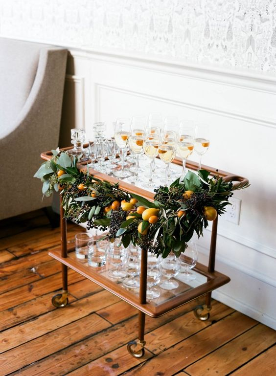 a decorated champagne cart - greenery and fresh citrus to make it chic