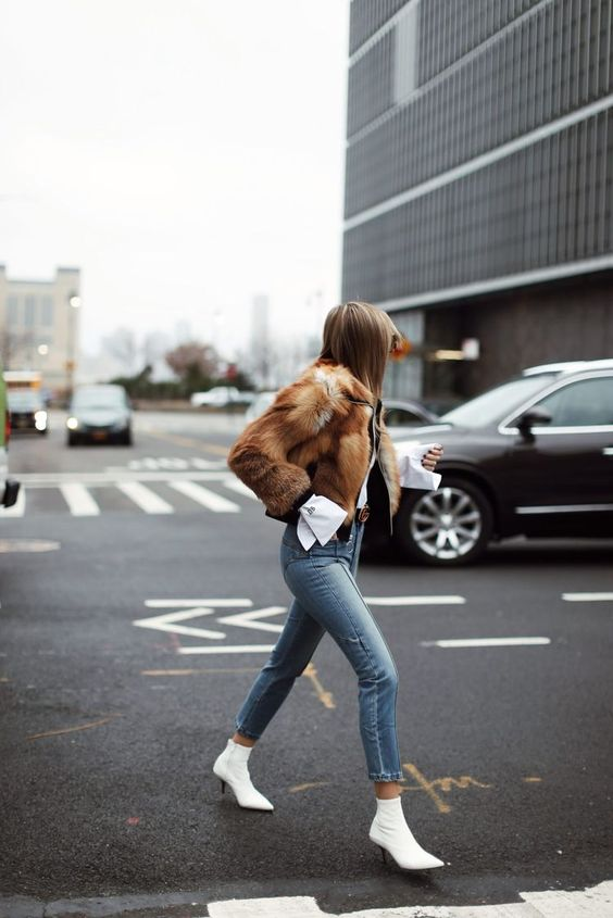 a white shirt, a black jacket, a faux fur coat, cropped jeans and white sock boots with kitten heels