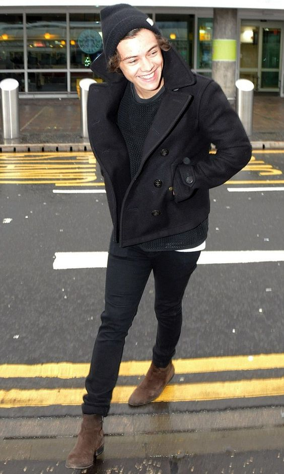 brown boots, a black sweater, black jeans, a black short coat and a beanie