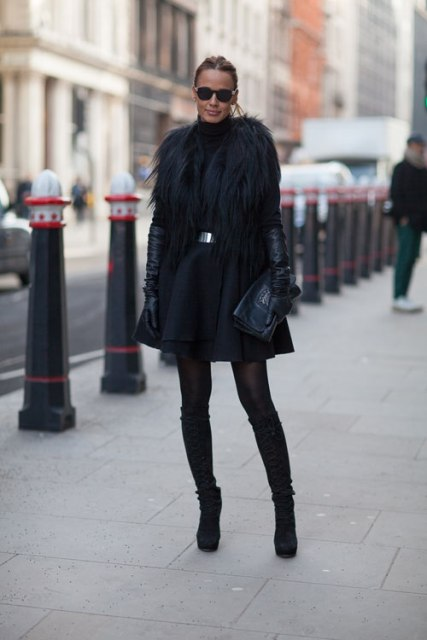 With black fur mini coat, high suede boots and clutch