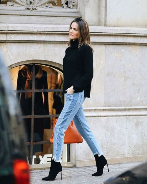 a black turtleneck sweater, light blue jeans and black suede sock boots