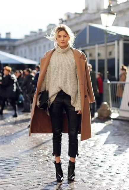 black cropped pants, a neutral turtleneck sweater, black booties and a camel coat