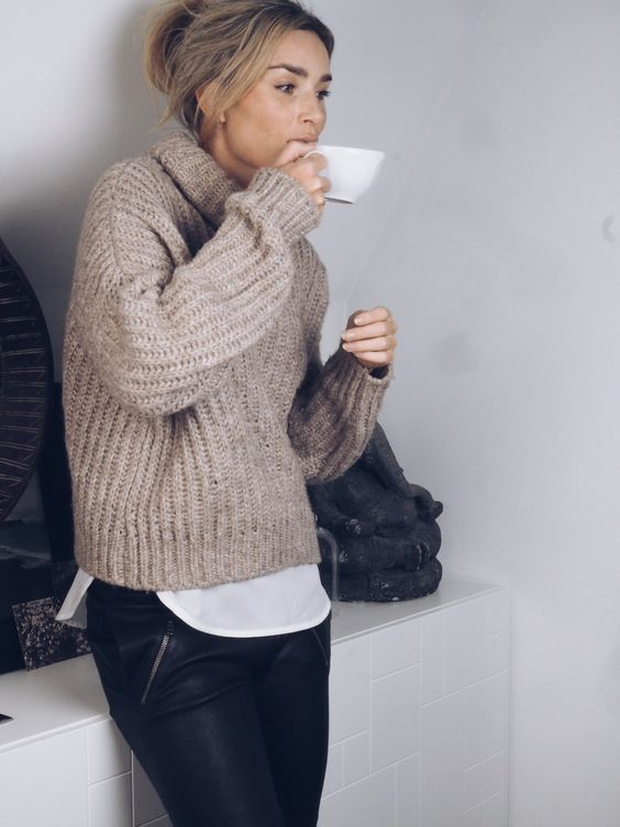 a neutral chunky knit sweater, a white shirt and black pants