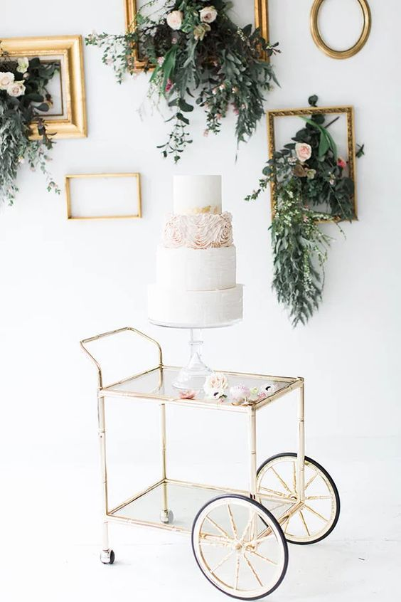 accentuate your wedding cake table with vintage frames and greenery and flowers attached to them