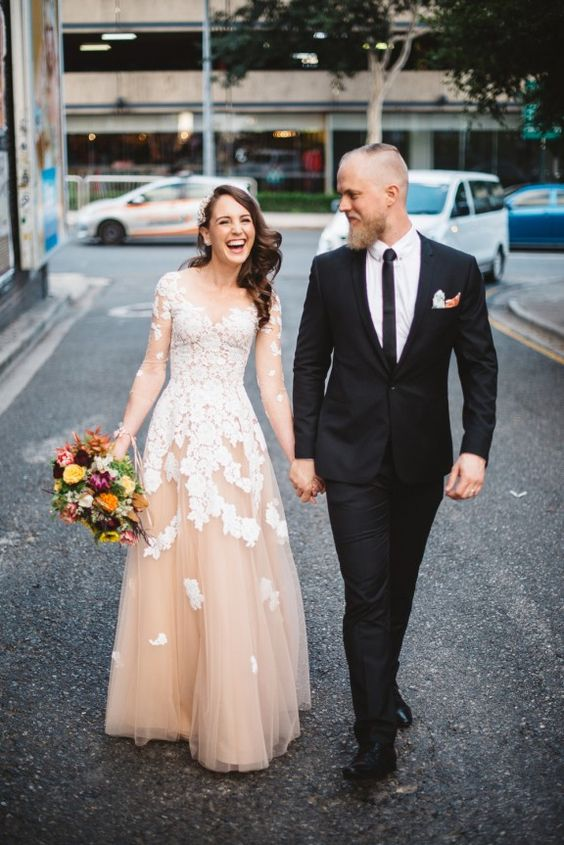 a blush wedding dress with an illusion neckline, sleeves and white lace appliques all over the dress