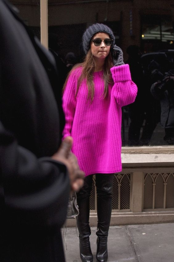 a neon pink chunky knit long sweater, black leather pants and boots and a black beanie