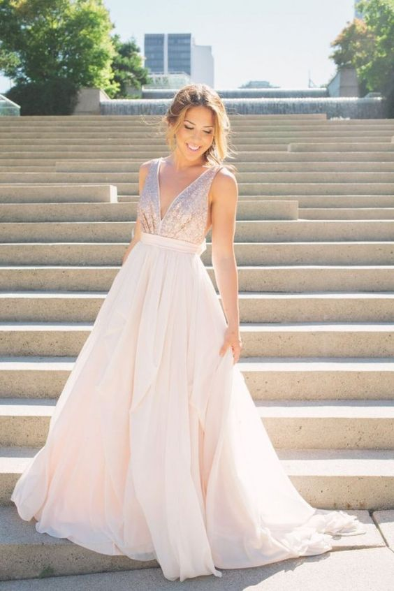 a sleeveless blush wedding gown with a sequin bodice and a plain full skirt, a plunging neckline