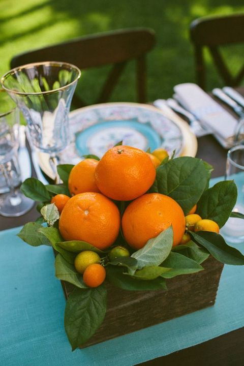 a wooden box with oranges and other citrus and foliage can become a nice and simple centerpiece