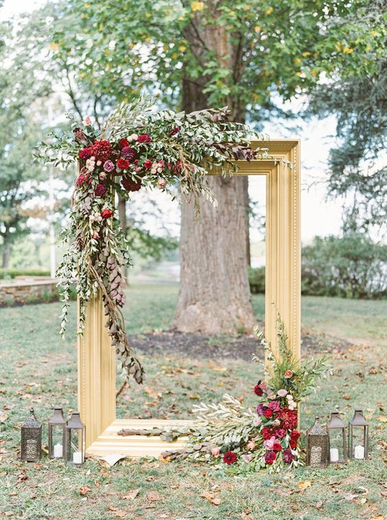 a refined backdrop with a large gilded frame, lush greenery and bold burgundy blooms plus candles around