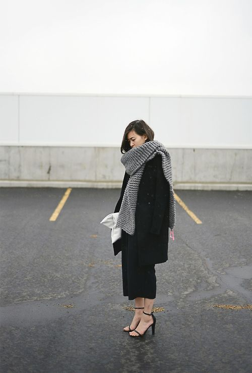 a grey chukny knit scarf worn over a black coat for a timeless look