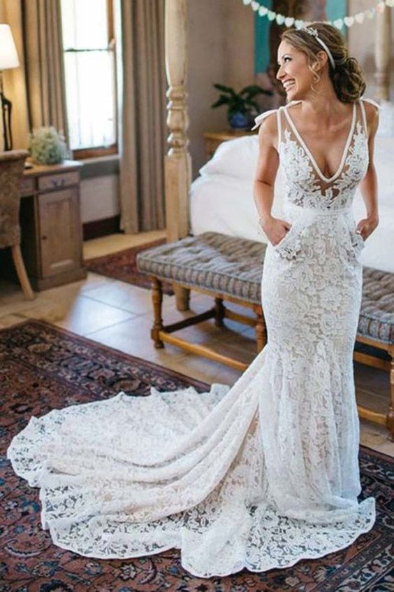 a sleeveless lace mermaid wedding dress with a deep V neckline, pockets and a train