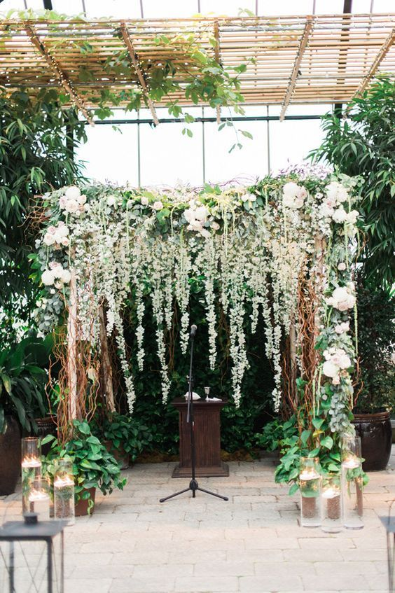 a gorgeous lush floral and greenery backdrop with an arch to feel like outdoors