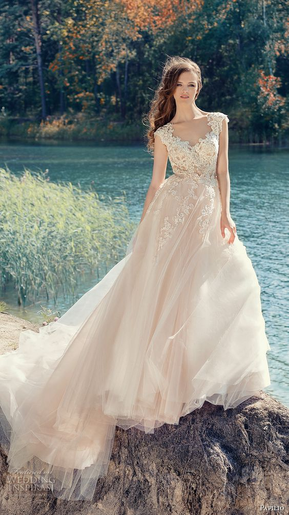 a blush cap sleeve wedding dress with a lace applique bodice and a full layered skirt