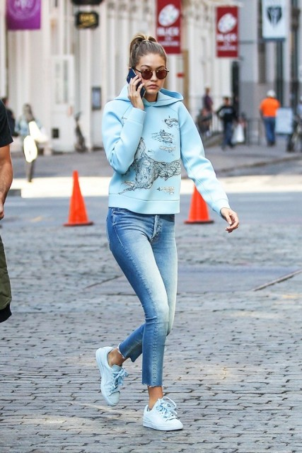 With light blue hoodie and sneakers