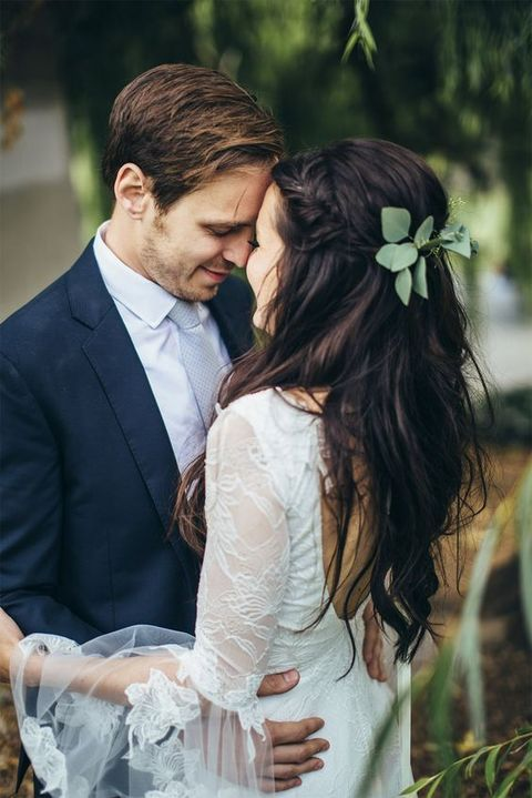 messy wavy braided half updo with fresh foliage is great for a boho or modern bride