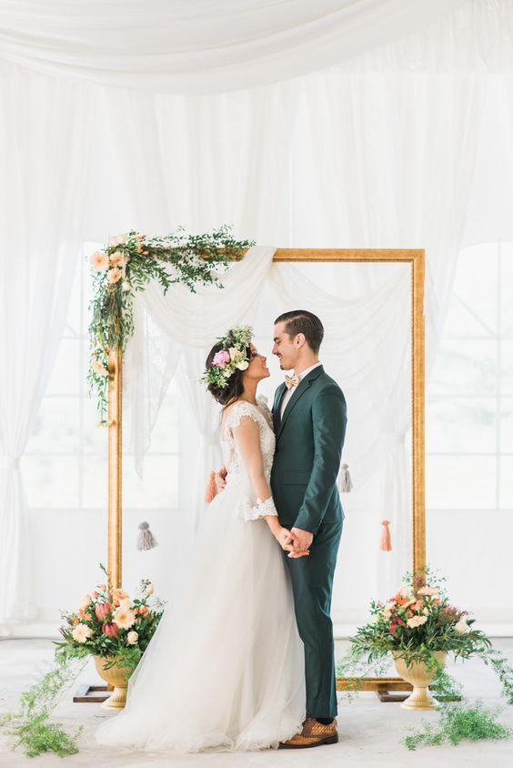 an ethereal draped fabric backdrop, an oversized picture frame decorated with greenery and blooms