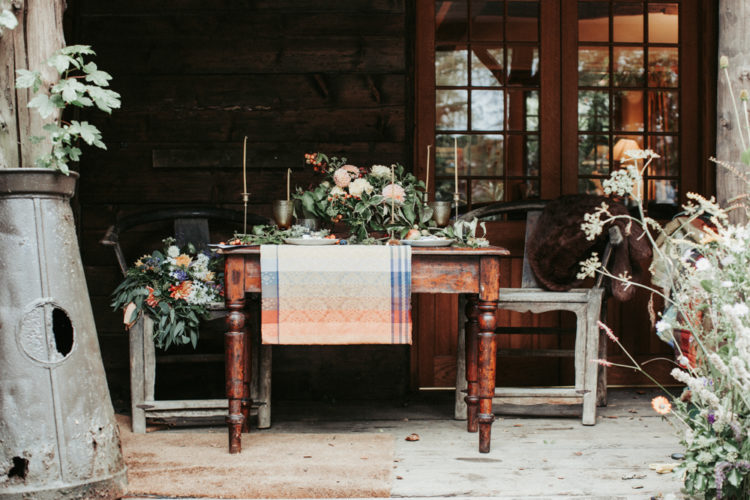 The wedding tablescape is done with a plaid runner, fall-like florals and vintage glasses