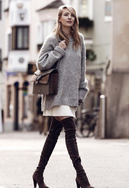 an oversized grey sweater over a white mini skirt, dark brown suede tall boots and a brown bag