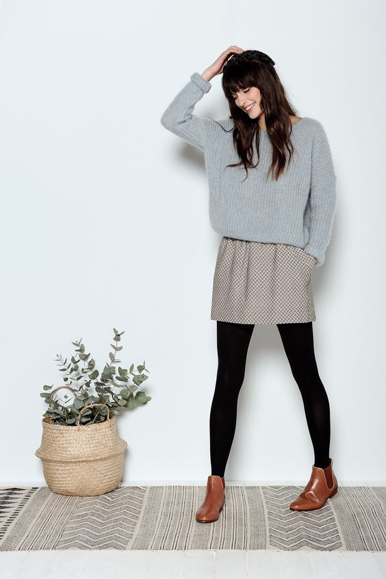 a printed mini skirt, an oversized grey sweater, black tights and amber chelsea boots