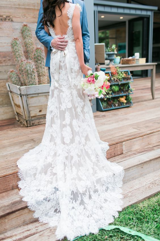 a lace wedding dress with no sleeves, an open back and a small train and a bridal sash
