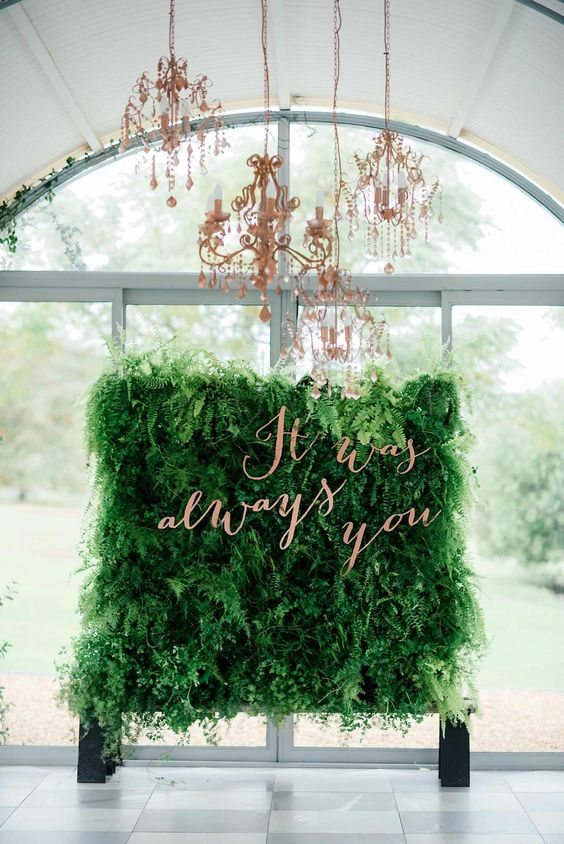 a lush living wall backdrop with copper calligraphy and a glam copper chandelier will catch an eye