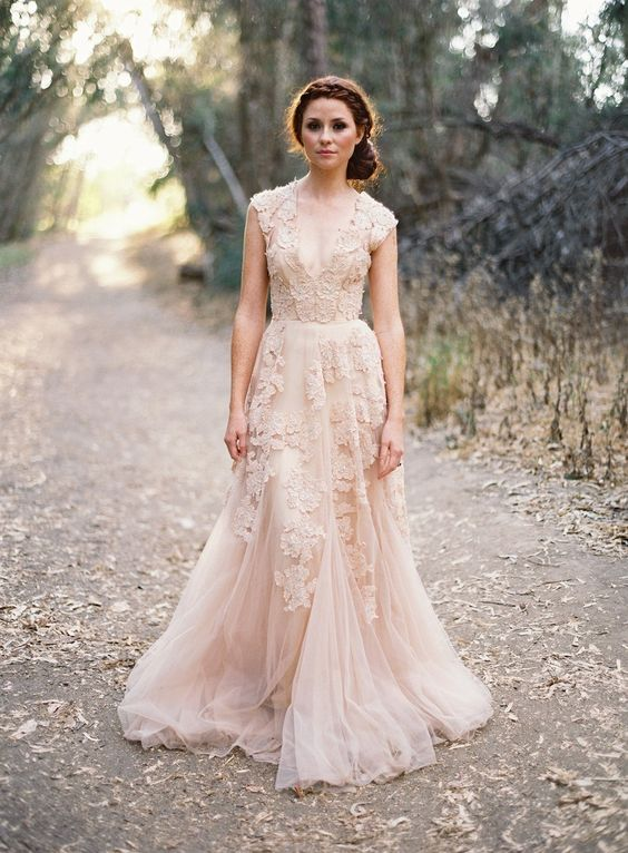 a sleeveless blush pink wedding dress with lace appliques and a deep V-neckline lookf super chic