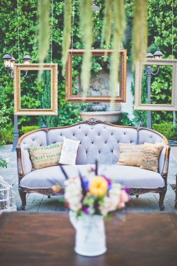 a wedding lounge with a lilac sofa and hanging picture frames over it for a chic feel
