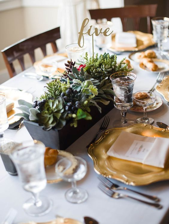 a lush centerpiece with succulents, foliage and privet berries plus a calligraphy table number