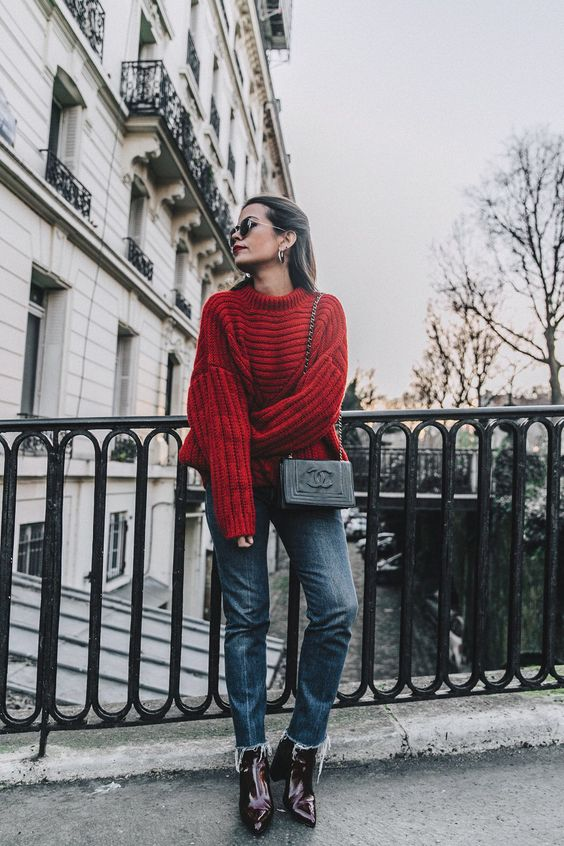 a red oversized sweater, blue jeans, burgundy boots and a Chanel bag