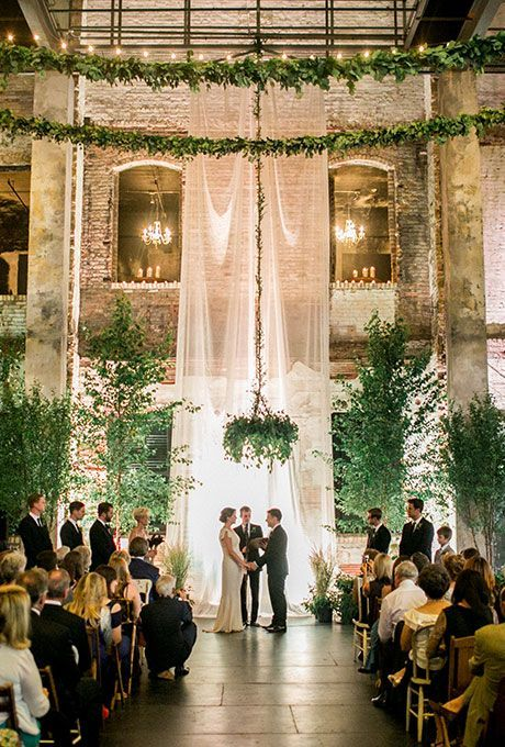 an ethereal curtain, lots of greenery around and greenery chandliers completely change the industrial venue