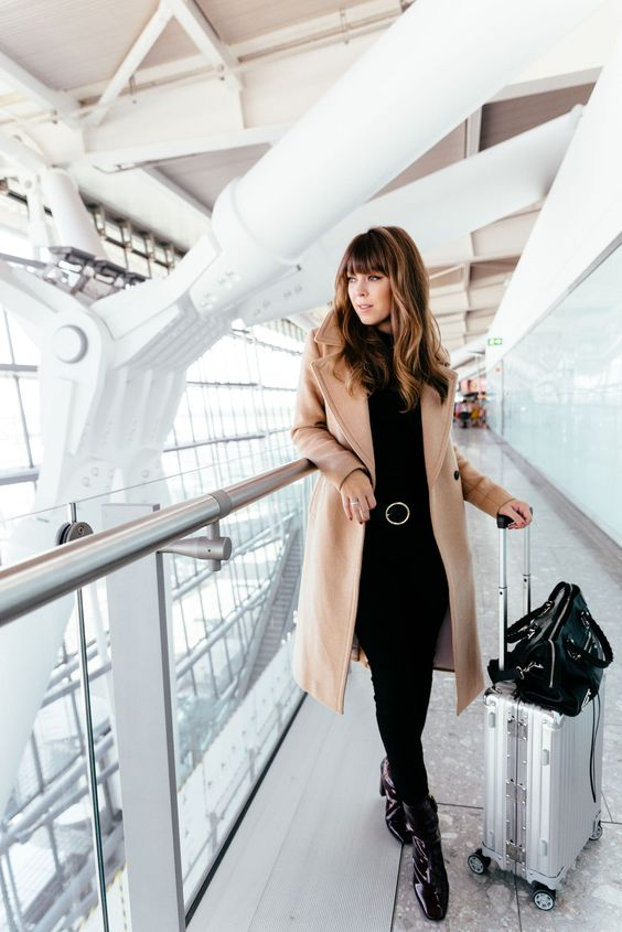 all-black look with jeans, a top, boots and a camel coat for a modern and comfy look