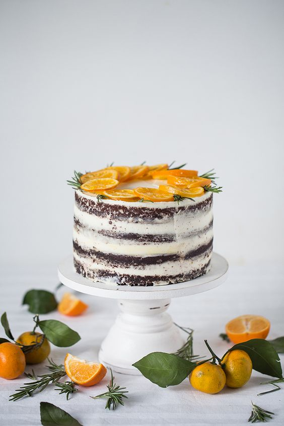 a semi naked wedding cake topped with fresh orange slices and rosemary is a tasty piece