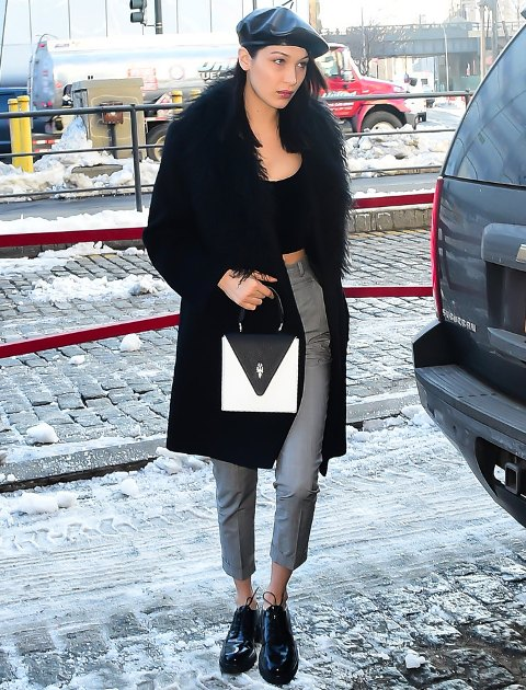 With black top, gray cuffed trousers, flat boots, fur coat and two color bag
