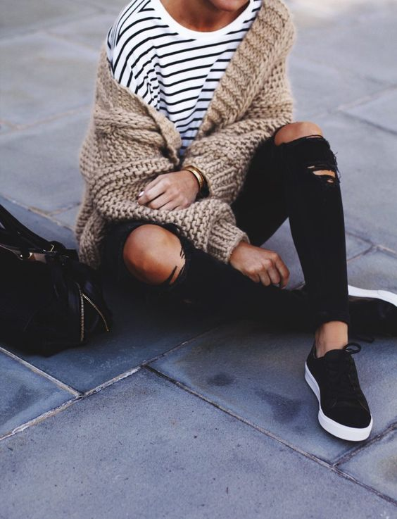 ripped black jeans, a striped top, black sneakers and a beige chunky knit cardigan
