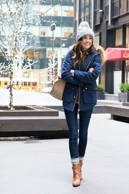 With gray beanie, skinny jeans, brown ankle boots, beige bag and brown sweater