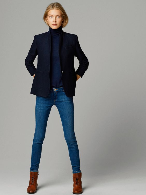 a navy turtleneck, a black blazer, blue jeans and brown boots