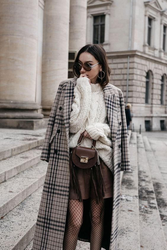 a white chunky knit sweater, a brown leather mini, tights, a plaid coat