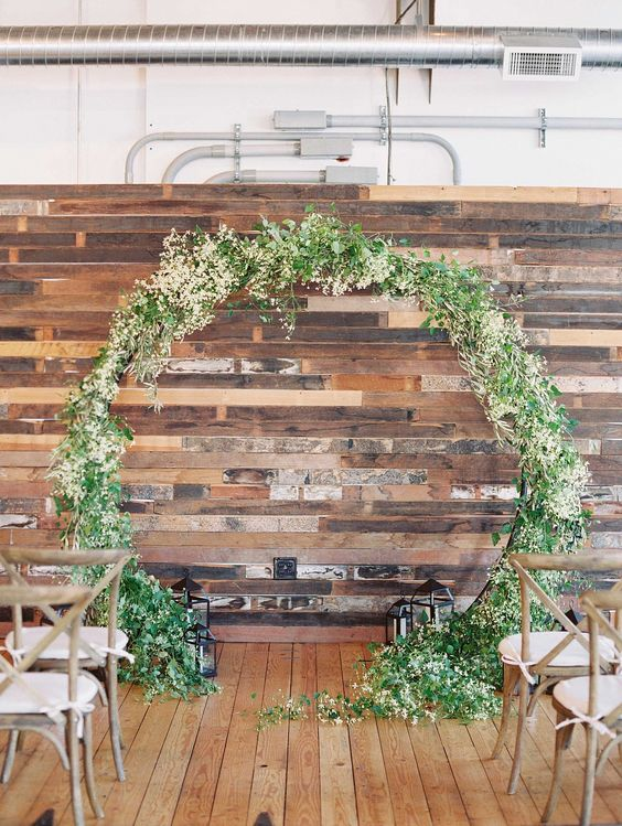 a reclaimed wood wall, candle lanterns and a greenery and bloom weddign arch for an outdoor feeling indoors